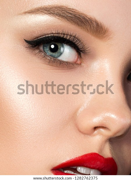 Portrait of young beautiful woman with evening make up. Red lips and eyeliner. Classic makeup concept. Studio shot. Extreme closeup, partial face view