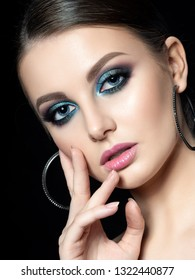Portrait of young beautiful woman with fashion makeup touching her face. Modern blue smokey eyes make up. Studio shot