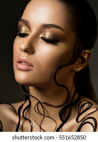 Portrait of young beautiful woman with fashion golden makeup and wet hair. Beauty studio shot.