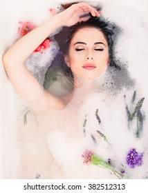 Portrait of young beautiful woman with flowers in the foam bath