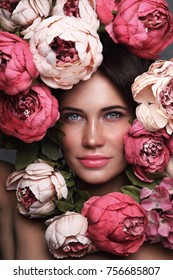 Portrait of young beautiful woman with flowers around her face