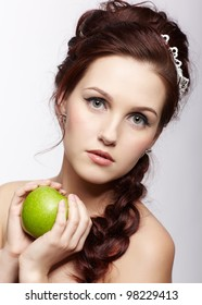 portrait of young beautiful woman with green apple on gray