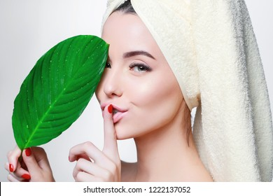 Portrait of young beautiful woman with healthy glow perfect smooth skin holds green tropical leaf. Organic, natural cosmetics, skincare, wellness, beauty clinic, facial treatment, cosmetology concept.