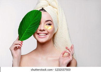 Portrait of young beautiful woman with healthy glow perfect smooth skin holds green tropical leaf. Gold cosmetics collagen hydrogel patch. Lifting anti-wrinkle mask under eyes. Skincare concept.