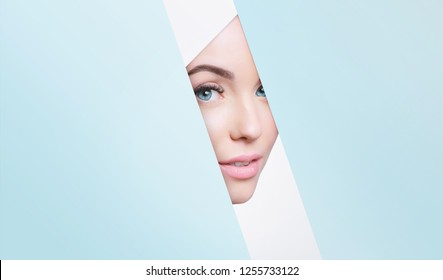 Portrait of young beautiful woman with healthy glow perfect smooth skin look into the hole of colored paper. Model with natural nude make up peers into hole in blue paper. Fashion, beauty, skincare.