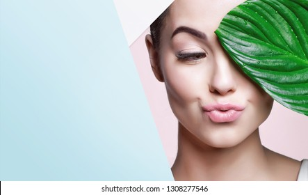 Portrait of young beautiful woman with healthy glow perfect smooth skin holds green tropical leaf, look into the hole of colored paper. Model with natural nude make up. Fashion, beauty, skincare.