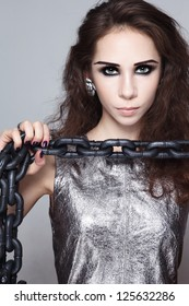 Portrait of young beautiful woman with heavy chain in her hands