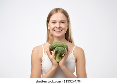 Portrait of a young beautiful woman holding green broccoli in her hands, isolated on white.