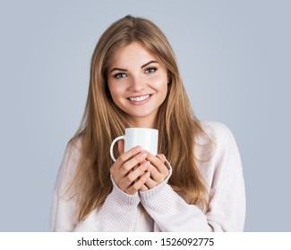 Portrait of a young beautiful woman holding a cup, isolated on grey