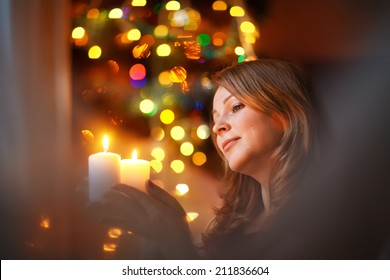 A portrait of a young beautiful woman holding a candle and looking at it with twinkling fairy lights as a background. Christmas.