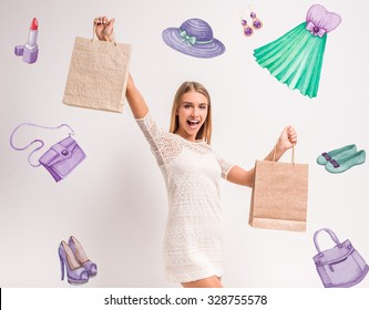 Portrait of a young, beautiful woman, holding a hand bag for shopping, gray background. Studio shoot