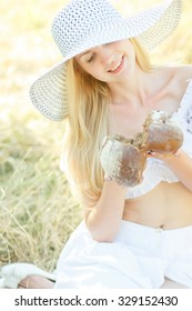 portrait of young beautiful woman holding fresh tasty bread in summer green park. soft focus