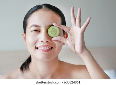 Portrait of a young beautiful woman holding cucumber slices on her eyes.