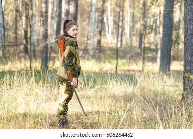 portrait Young beautiful woman hunter with a shotgun in the forest, hunter in camouflage clothes ready to hunt with hunting rifle