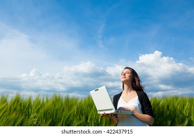portrait of young beautiful woman with laptop in the field