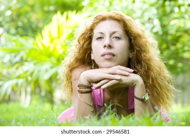 Portrait of young beautiful woman  laying on green grass