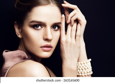 Portrait of young beautiful woman with light makeup and blue eyes touching her face. Dark background. Wearing pearls bracelet and earrings.