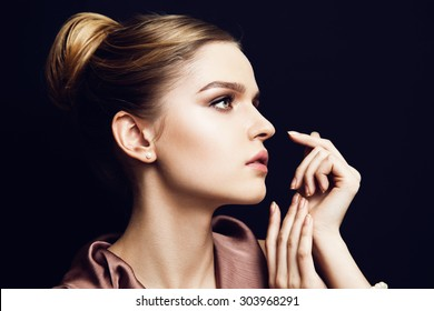 Portrait of young beautiful woman with light makeup and blue eyes almost touching her face, looking to the side. Dark background. Wearing pearls bracelet and earrings.