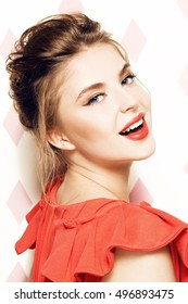 Portrait of young beautiful woman with light  eye makeup and red lipstick. Smiling. Looking at the camera. Wearing red dress. Pink rhombus background.