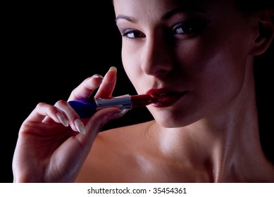 portrait of a young beautiful woman with lipstick in their hands against a dark background