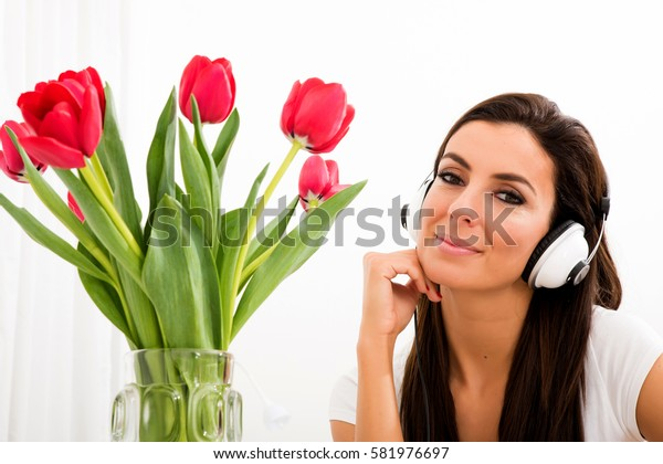Portrait of a young beautiful woman listening to music with tulips in the background
