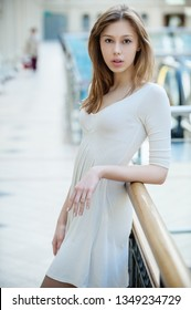 Portrait of young beautiful woman with long hair near wooden railing.
