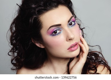 Portrait of young beautiful woman with long curly hair and fancy make-up