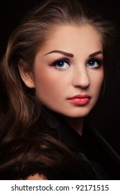 Portrait of young beautiful woman with long curly hair and stylish make-up