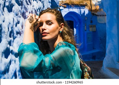 portrait of young beautiful woman lying on a blue wall of a blue street of moroccan city