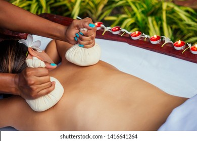 Portrait of young beautiful woman lying on a wooden table in spa environment flowers and candles
