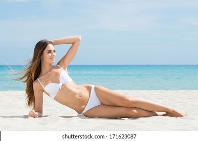 Portrait Of A Young Beautiful Woman Lying On Sand At Beach