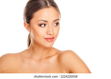 Portrait of young beautiful woman with makeup looking aside on white background