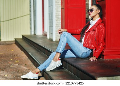 Portrait of a young beautiful woman on a city street . The model is dressed in a stylish leather biker jacket, turtleneck, blue jeans