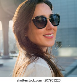 Portrait of a young beautiful woman on a city-scape background