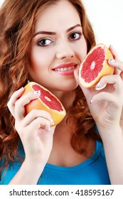 Portrait of a young beautiful woman on a white background. Young woman holds halves of grapefruit. Citrus.