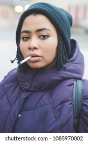 portrait young beautiful woman outdoor looking camera smoking cigarette - unhealthy lifestyle, rebel, attitude concept