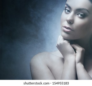Portrait of young and beautiful woman over smoky background