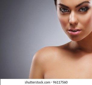 Portrait of young and beautiful woman over grey