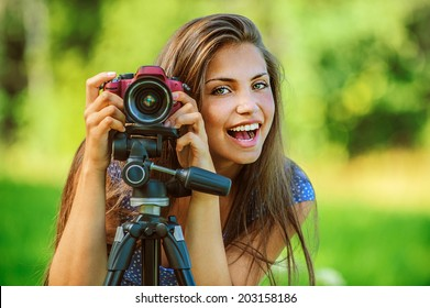 Portrait of young beautiful woman photographed with camera tripod, on green background summer nature.