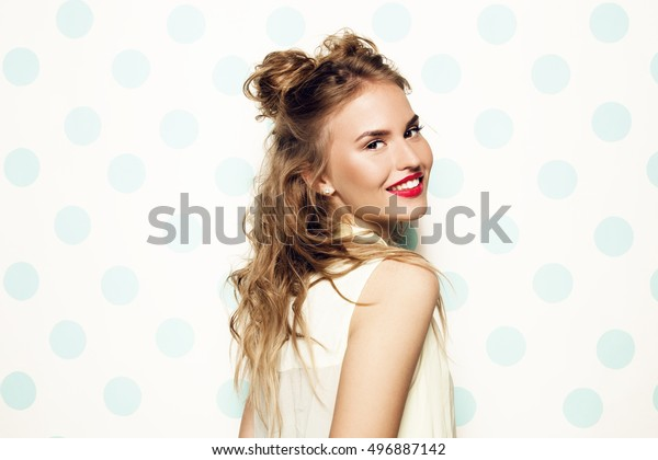 Portrait of young beautiful woman with pink lipstick, curly long hair and playful hairstyle. Smiling. Mint polka dots background.