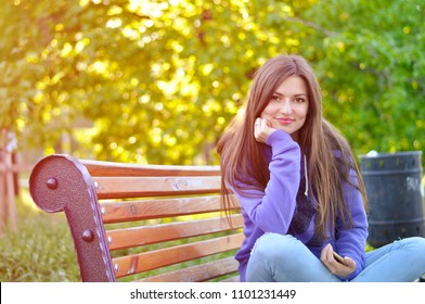 portrait of a young beautiful woman in a purple sports blazer that sits on a bench in the park and smiles