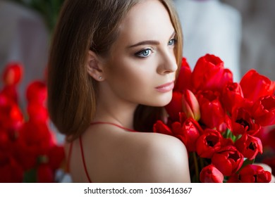 Portrait of young beautiful woman in red dress with tulips in luxury interior.