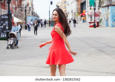 Portrait of a young beautiful woman in red dress walking in summer street