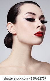 Portrait of young beautiful woman with red lips and cat eyes make-up