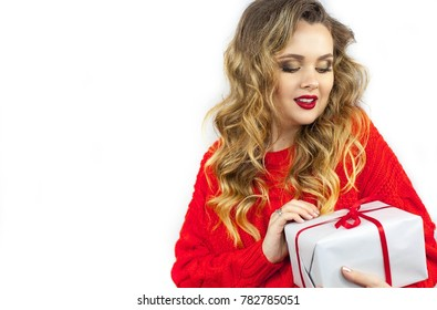 Portrait of a young beautiful woman. A young woman in a red sweater with a red lipstick holds a present. Makeup. Holidays. Valentine's Day. Christmas. New Year. Beauty.