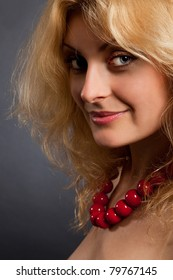 Portrait of young beautiful woman with red necklace on a black background