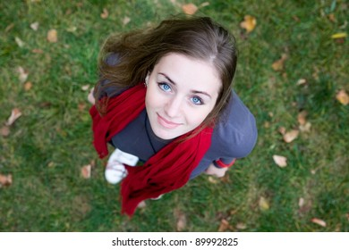 Portrait of a young beautiful woman in red color scarf on grass.  Top view