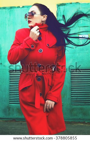 949b825a4d7 portrait of young beautiful woman in red coat and sunglasses. photo with  color filter.