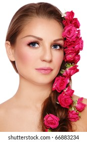Portrait of young beautiful woman with rose in hair, on white background