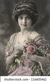 portrait of young beautiful woman with roses flowers. vintage picture from 1911